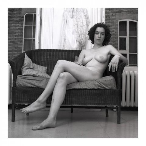 Jeune femme brune assise dans un canapé en osier. Québec 1988