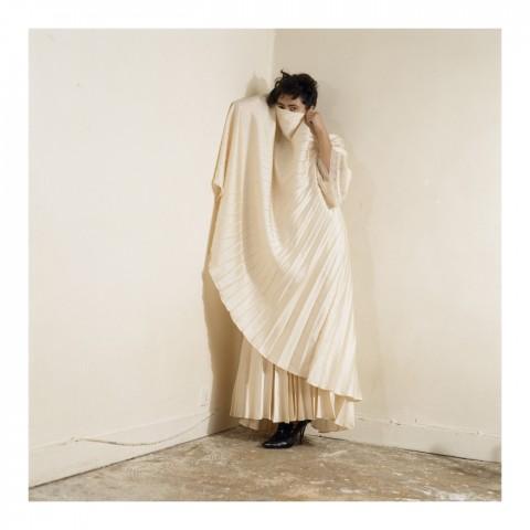 Jeune femme brune cachant son visage derrière un pan de sa robe blanche. Paris 2005