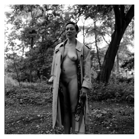 Jeune femme portant un imperméable ouvert, au bois. Photographie en noir et blanc